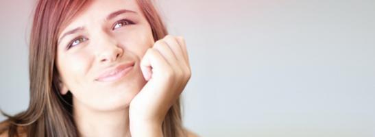 Bild på en ung kvinna som ser fundersam ut. Bilden illustrerar att det är vanligt att ha många frågor i samband med puberteten, om mens eller tamponger.