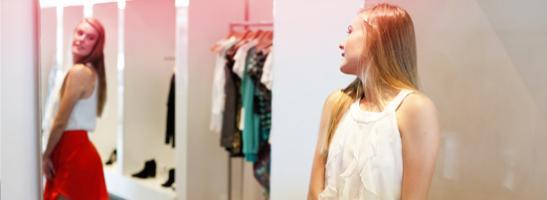 Ung kvinna står framför en spegel och provar nya kläder. Bilden illsutrerar hur en ung kvinnas kropp förändras under puberteten.