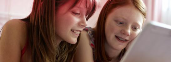 Bild på två unga flickor som sitter framför en dator. Bilden illustrerar att det är vanligt att ha många frågor, och på o.b.®'s hemsida kan du hitta information om den första mensen, puberteten och annan bra information