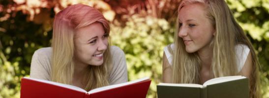 Bild på två unga kvinnor som läser vars en bok. Bilden illustrerar de många myter det finns i samband med menstruation.