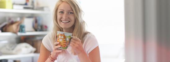 Bild på en ung kvinna som håller i en kopp.