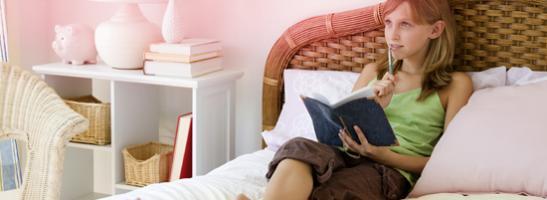 Bild på en ung kvinna som sitter i sin säng och gör anteckningar. Bilden illustrerar att det finns många frågor kring den första mensen, men det är inget att oroa sig för !