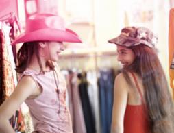 Bild på två unga flickor som provar kläder. Bilden illustrerar hur flickor utvecklas och blir kvinnor.